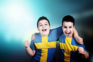 Two adorable boys soccer fans with flag of Sweden on t-shirt, embracing celebrate the victory of his team. Happy and shout. Stadium lights in the background. Blue background. Landscape orientation.